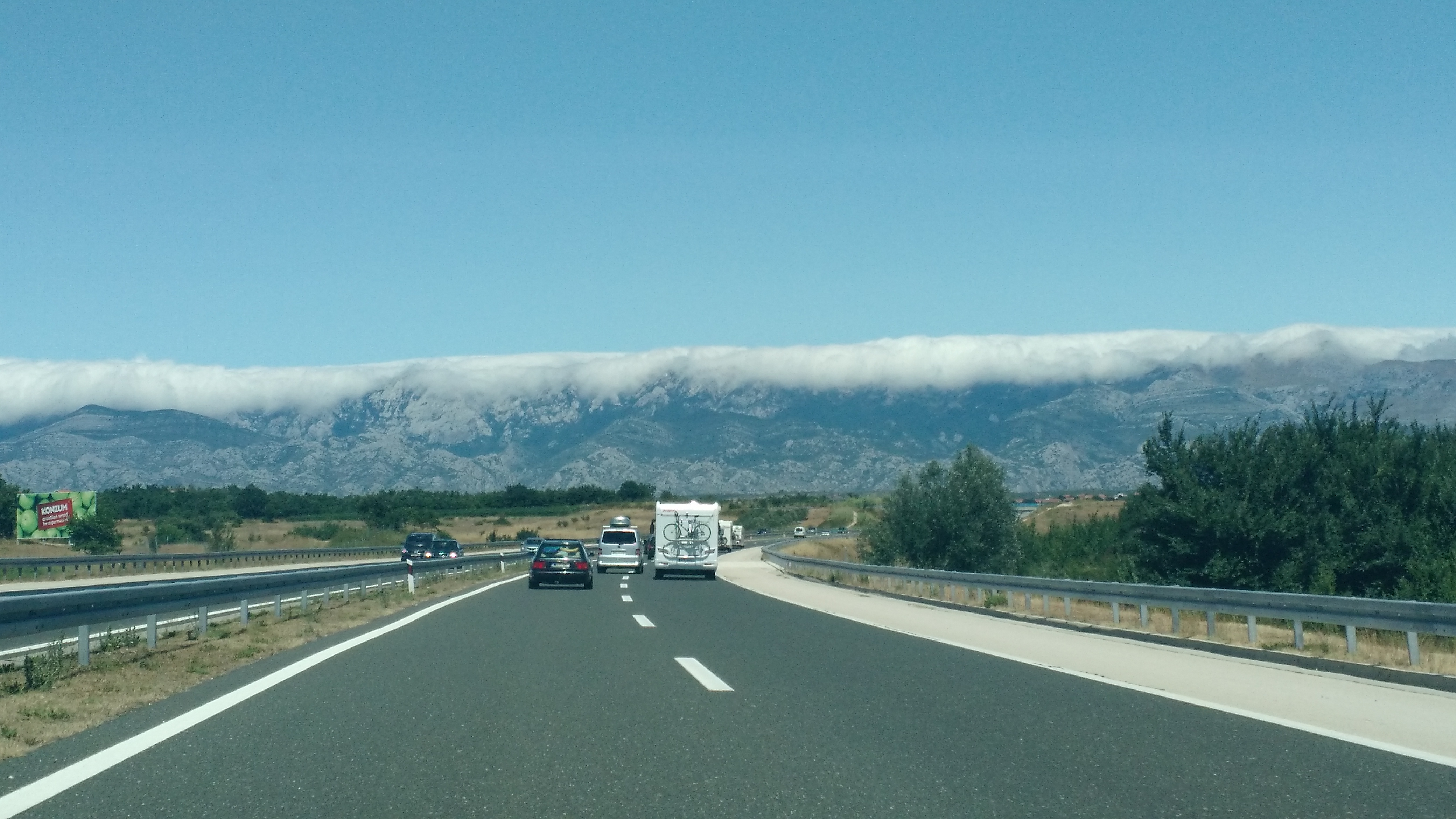 Clouds skimming the tops of mountains along the highway